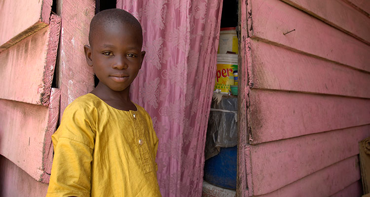 An African boy standing in the doorway of his home. The photography of Compassion International shows the dignity and hope living within the poor despite the oppression poverty inflicts upon them.